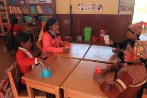 Niños y niñas de Huarahura Trabajndo ejercicios de coordinación con vasos